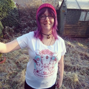 """Em Saanen standing out in her garden. She is wearing a red beanie hat and at t-shirt with a """"Friends Not Food"""" design on it."""
